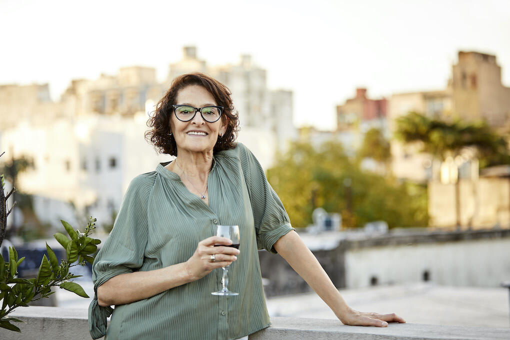 Portrait of smiling senior woman having red wine. Retired female is wearing casuals. She is standing on terrace.